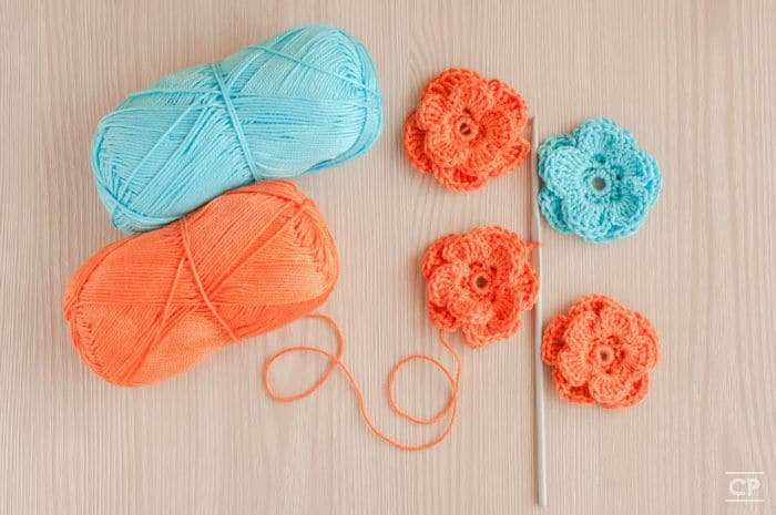 Aqua and orange yarn with crocheted flowers and crochet hook