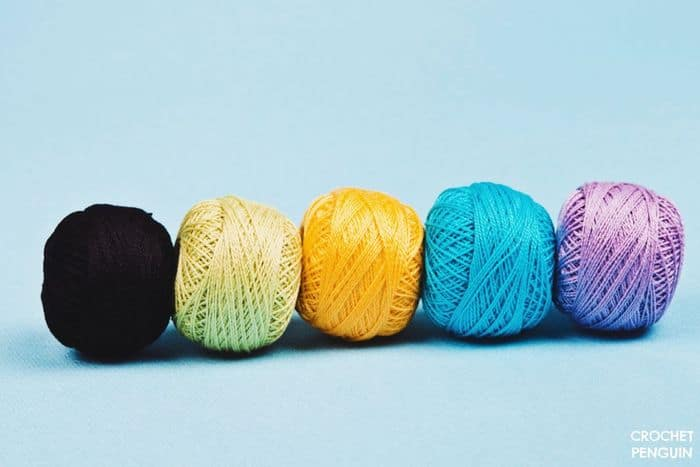 Colorful crochet balls of crochet thread in a row, black, lime, yellow, turquoise, purple