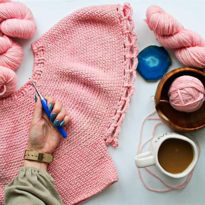 Furls Blue Odyssey Crochet Hook in a crocheter's hand on a pink sweater