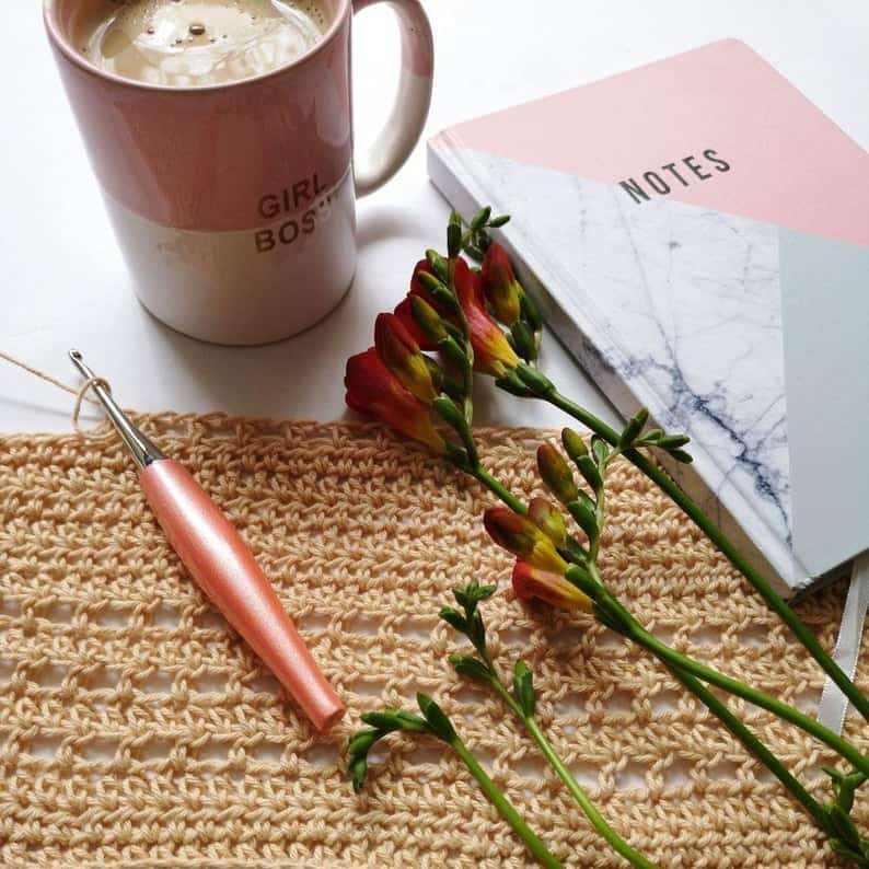 Furls Crochet Peach Odyssey and Nickel Hook. Crochet project, notebook and mug of coffee